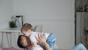 Папа и сын обнимают падать в кровать совместно, замедленное движение сток-видео