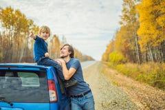 Папа и сын отдыхают на стороне дороги на поездке Поездка с концепцией детей стоковые фото