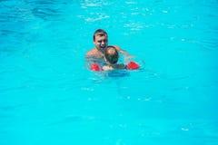 Папа и сын плавая совместно в бассейне стоковое фото