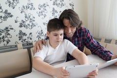 Папа и сын с планшетом крытым стоковое фото