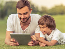 Папа и сын с устройством Стоковое фото RF