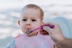 Папа кормит младенца с ложкой каши outdoors Ребенок messing но счастливый стоковое изображение rf