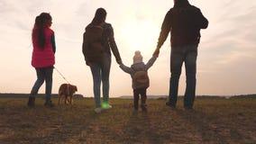 Папа, мама, небольшой ребенок и дочери и туристы любимцев сыгранность дружной семьи перемещения семьи с собакой дальше сток-видео