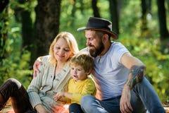 Отец матери и меньший сын сидят пикник леса Хороший день для пикника весны в природе Исследуйте природу совместно Семья стоковое изображение