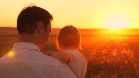 Папа носит его маленькую дочь в его оружии, освещенном лучами красивого захода солнца Счастливая семья идет в парк в лете видеоматериал