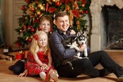 Папа, дочь и сын с осиплыми щенятами на рождестве сидя дальше стоковое изображение