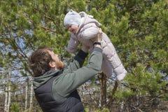 Папа поднимает его дочь наверху Newborn в прозодеждах в оружиях счастливого папы Молодой отец с ребенком стоковое изображение