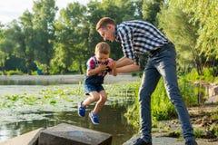 Папа поднимает его маленького сына в его оружиях на предпосылку реки Стоковые Фотографии RF