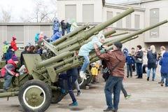 Папа помогает дочери получить с зенитного оружия, которое стоит около музея мемориала победы стоковые изображения