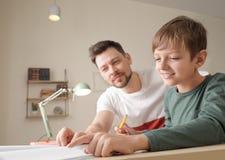 Папа помогая его сыну с назначением школы стоковые изображения