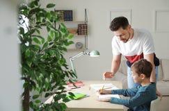 Папа помогая его сыну с назначением школы стоковые изображения rf
