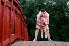 Папа при его маленькая дочь стоя на деревянном мосте стоковая фотография rf