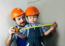 Папа при маленький сын делая ремонты стоковые фотографии rf