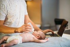 Папа пробуя работать пока стоящ с его newborn малышом в интерьере домашнего офиса стоковое изображение rf