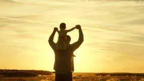 Папа продолжает плечи его любимого ребенка, в лучах солнца Отец идет с его дочерью на его плечах в лучах акции видеоматериалы