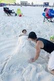 Папа строит замок песка русалки вокруг его дочери Стоковые Изображения RF