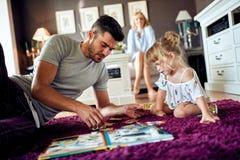 Папа с дочерью играя с головоломками стоковая фотография