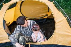 Папа с его маленькой дочерью в шатре на располагаться лагерем стоковое фото rf