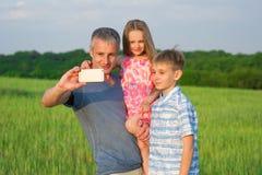 Папа с детьми делает selfie на телефоне стоковые фотографии rf