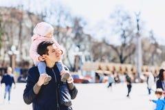 папа с младенцем на плечах идет на улицу Стоковая Фотография