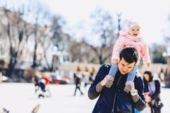 папа с младенцем на плечах идет на улицу Стоковое Изображение