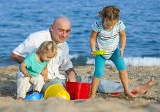 Папа с дочерьми на пляже моря Стоковое фото RF