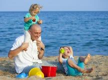 Папа с пляжем дочерей на море стоковые фото