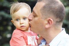 Папа целуя его сына стоковые фото