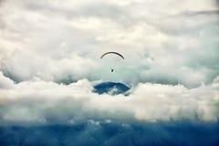 Параглайдинг среди облаков над горной цепью Стоковое фото RF