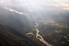 Параглайдинг среди облаков над горной цепью Стоковые Изображения