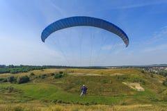 Параплан летая вниз с холма Стоковые Фотографии RF