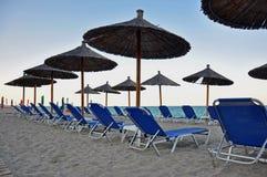 Парасоли и deckchairs на пляже Стоковые Изображения RF