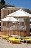 Парасоли и deckchairs на пляже Стоковая Фотография