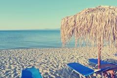Парасоли и loungers солнца на белом песчаном пляже; увяданный, ретро стиль Стоковое Изображение RF