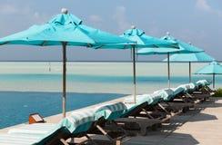 Парасоль и sunbeds морским путем на пляже Мальдивов Стоковые Изображения