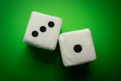 Пара белого плюша dices на зеленой предпосылке Стоковые Изображения