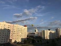 Парад воздушных шаров над городом Аэростаты других цветов летают в голубое небо над домами Стоковое Изображение