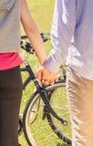 Пара вручает крупный план над предпосылкой велосипедов колеса Стоковое Фото