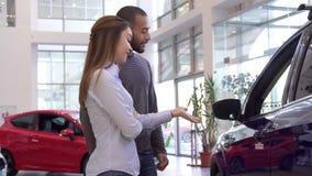 Пара выбирает автомобиль на дилерских полномочиях стоковые фотографии rf