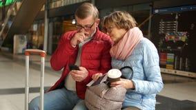 Пара выбытых путешественников примирить их билеты с расписанием поезда используя их смартфон пары зреют самомоднейшее сток-видео