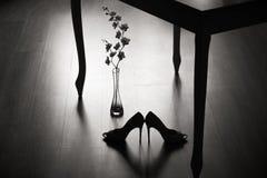 Пара высоких пяток и цветка под таблицей стоковое фото rf