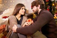 Пара в влюбленности дома давая представляет ночу рождества Стоковые Изображения