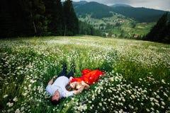 Пара в влюбленности кладет на луг стоцвета и наслаждается красивым взглядом ландшафта гор и Стоковое Изображение
