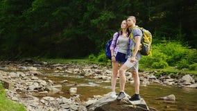 Пара в влюбленности восхищает красивый пейзаж, стойку на утесе около реки горы Перемещение и активный образ жизни видеоматериал