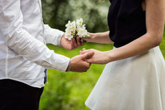 Пара в влюбленности вручает касающий цветок, цветок в bloss сада Стоковая Фотография RF