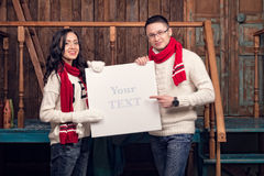Пара в зиме одевает держать белую пустую доску Стоковые Фотографии RF