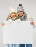 Пара в зиме одевает держать пустую доску стоковые изображения rf