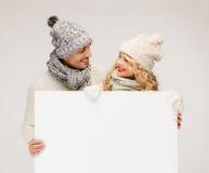 Пара в зиме одевает с пустой белой доской Стоковые Фотографии RF