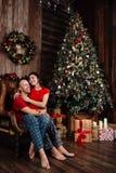 Пара в красных футболках и пижамах сидит в кресле рождественской елкой Стоковое Изображение