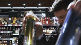 Пара в супермаркете принимает некоторые консервные банки пива сток-видео